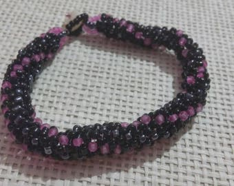 Bead woven bracelet in black, fuchsia and lead