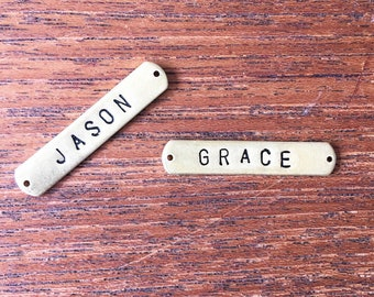 Sew on dog ID tags. Rounded edges. Golden brass metal plate with stamped name or phonenumber. Choose up to 10 letters or numbers