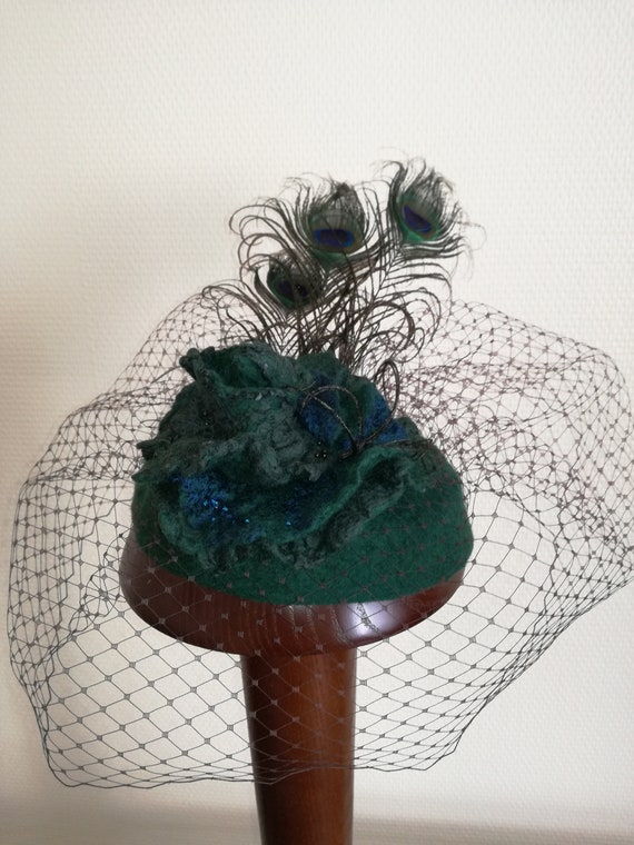 Hat in Merino Wool with a flower of pink, peacock feathers and veil.