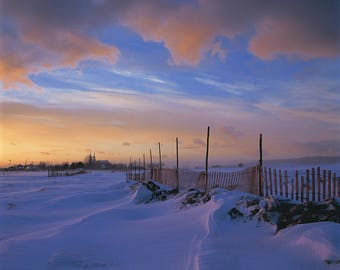Snowstorm, church and snow fence at sunset at Saint-Roch-des-Aulnaies, Chaudière-Appalaches