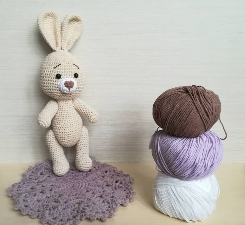crochet lovely Bunny with heart as toy for child. Stuffed Rabbit with decorative egg as Easter gift