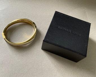 Michael Kors, gold bracelet with rhinestones.