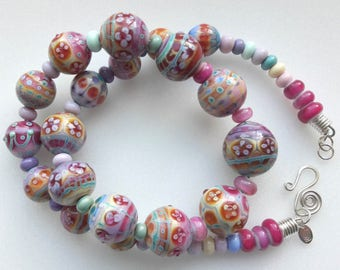 Intricately patterned, handmade, fabulous lampwork glass and silver necklace is in complementary shades of pink, turquoise and pale yellow.