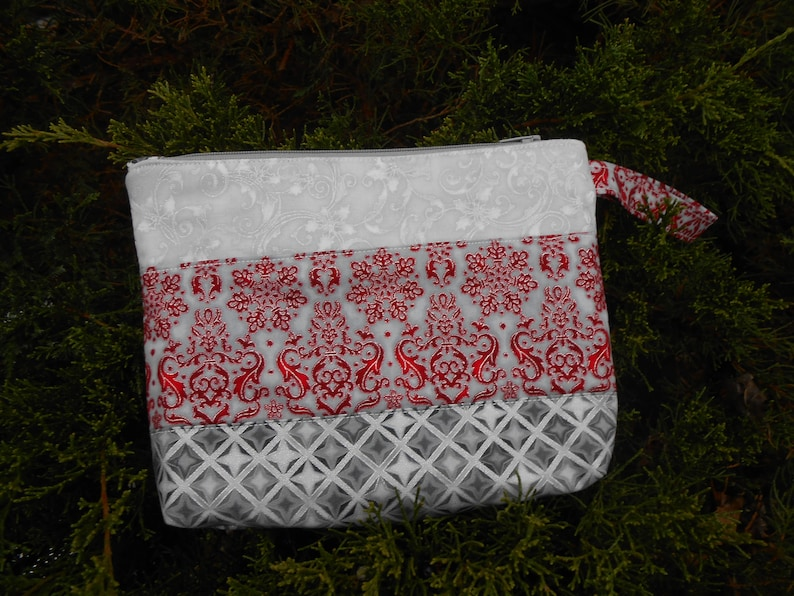 Pretty zipper pouches makes a nice gift for a lady Christmas colors of red or maroon with silver etching could use for evening pouch.