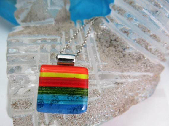It's a good look.  Glass fusion square, rainbow color, stainless steel chain. Hypoallergenic.