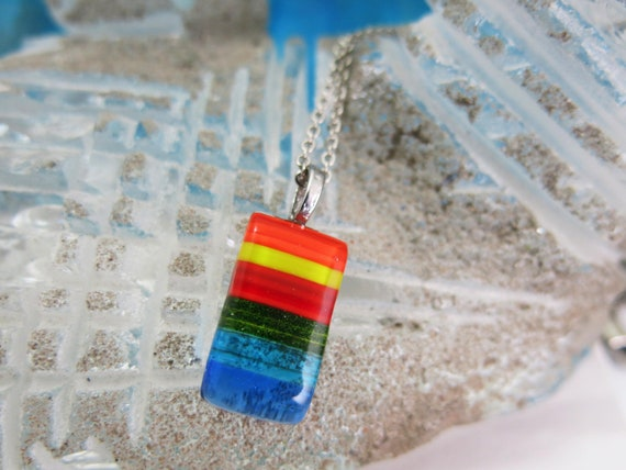 It's a good look.  Rectangle of fusion glass, rainbow color, stainless steel chain. Hypoallergenic.
