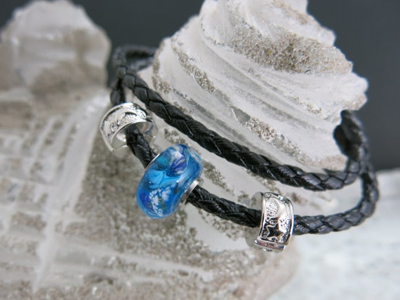 Braided black leather strap and turquoise blue glass beads spun with a blowtorch. Several size choices.
