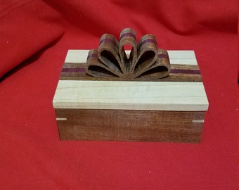 This is a Beautiful Keepsake Box that Features a Wooden Ribbon on it.