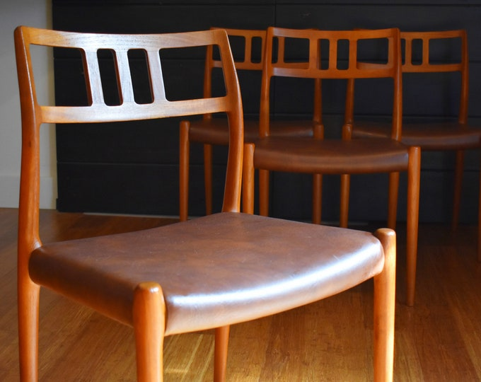 Four Danish teak Niels Moller 79 dining chairs w/brown faux leather