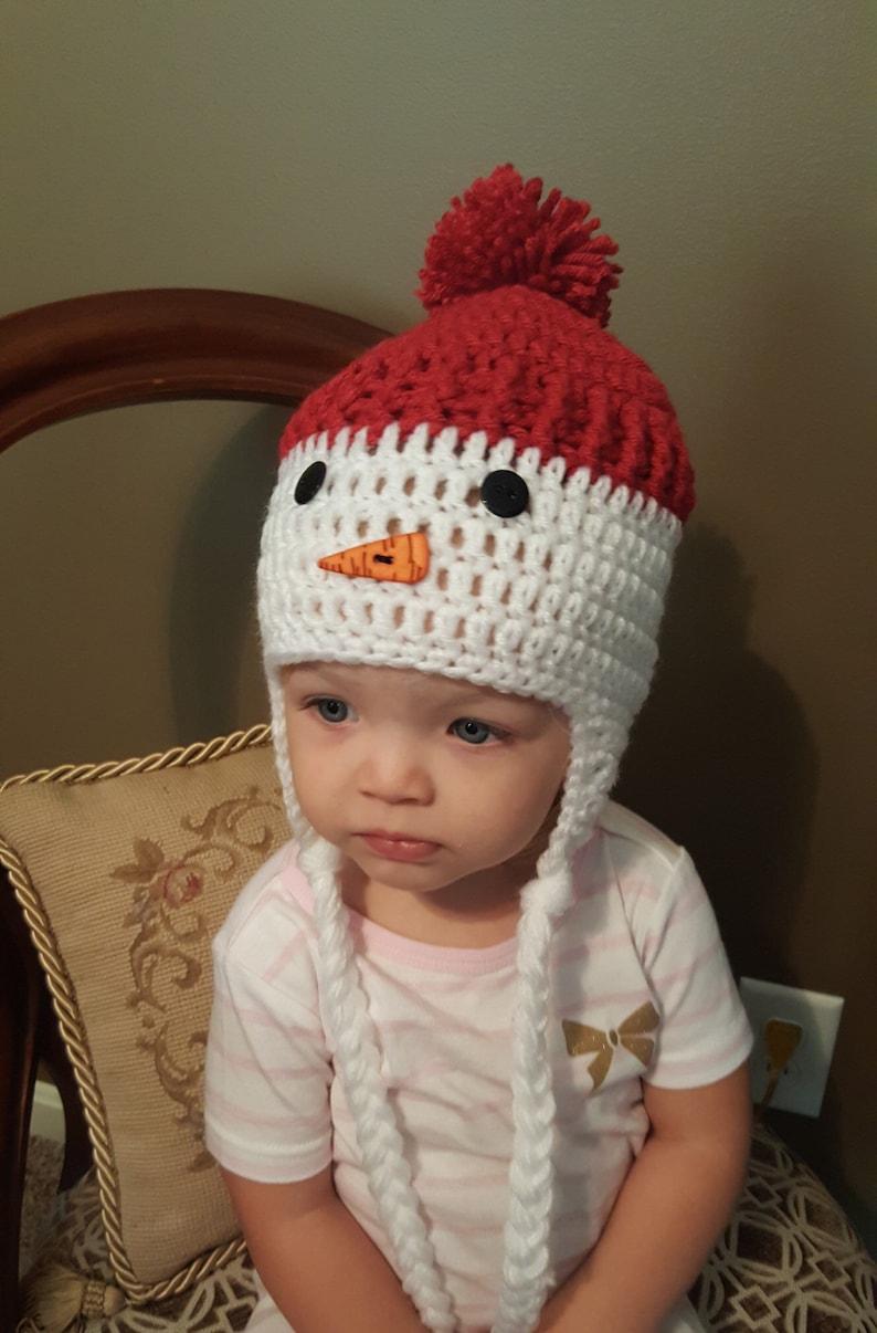 Crochet snowman hat with ear flaps.