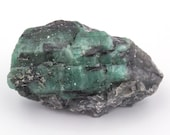 Raw emerald stone of 85 grams with matrix of black mica and quartz.