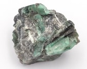 Raw emerald stone of 84 grams with matrix of quartz and black mica.