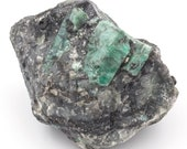 Raw emerald stone of 693 grams with matrix of black mica and quartz.