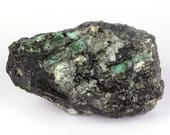 Raw emerald stone of 958 grams with matrix of black mica and quartz.