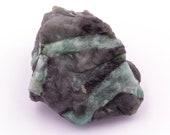 Raw emerald stone of 51 grams with matrix of quartz and black mica.