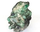 Raw emerald stone of 2020 grams with matrix of black mica and quartz.