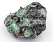 Raw emerald stone of 169 grams with matrix of quartz and black mica.