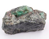 Raw emerald stone of 226 grams with matrix of black mica and quartz.