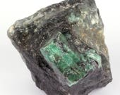 Big crystal of green emerald on black mica and quartz.