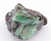 Raw emerald stone of 145 grams with matrix of quartz and black mica.