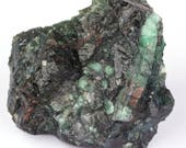 Raw emerald stone of 741 grams with matrix of black mica and quartz.