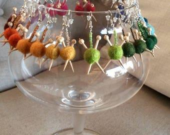 Earrings, felted wool ball of yarn and needle.