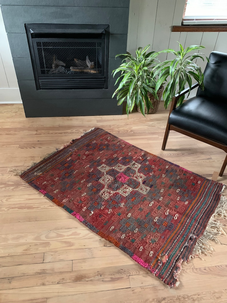 Maroon Vintage Turkish kilim rug with faded pink and a worn patina