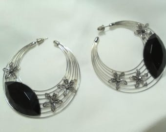 Flamenco earrings made on concentric hoops and adorned with metallic flowers and black faceted stone. are very original