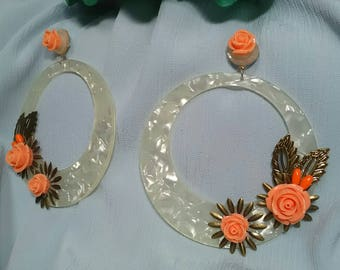 Flamenco earrings made with an ivory acetate base and adorned with metallic details and resin flowers in coral color.