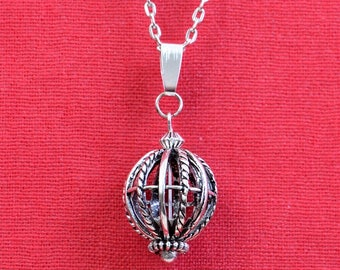 Ball cage and silver metal chain necklace with pendant