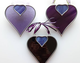 Handmade purple and black stained glass heart shaped decorative hangings.