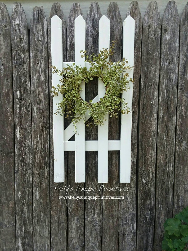 Give your fence a nice cottage look by adding rustic materials to it. Try a flower box, window frame, wreaths or other cottage decor. I think this is my favorite look! Here are some quick and easy ways to decorate your garden fence.