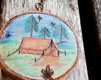 Camping keychain or ornament/gift tag, pyrography live edge birch slice, tent and campfire in a forest of trees, night time sky with stars