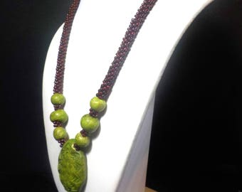 Rustic lime green beaded necklace with mahogany brown beads and a carved pendant, gold magnetic clasp