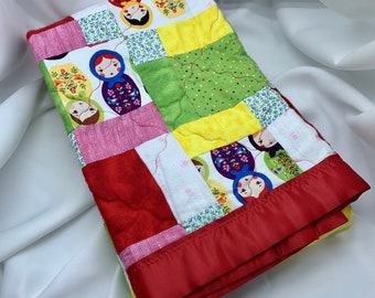 Hand made baby quilt with matryoshka doll motif juxtaposed to red and white polka dots.