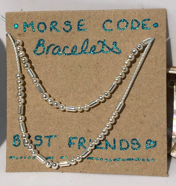 2 Handmade MORSE-Code bracelets. Best Friends. Fully adjustable. Silver plated beads on pale pink and blue coloured beadalon thread SRA J57