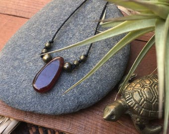 red garnet teardrop pendant on adjustable black cotton cord with brass beads