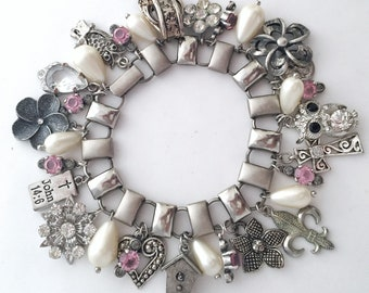 Silver charm bracelet.  Vintage assemblage using book chain and repurposed jewelry.  Owl, birdhouse, bible, flowers, rhinestones, heart.