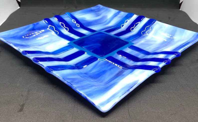 Southwestern style fused art glass plate made with blue and white streaky glass with indigo and cobalt blue accent pieces