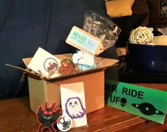 Cryptid-themed Mystery Box - Care Package with Mothman, Bigfoot, other cryptids - pins, buttons, bathbombs, keychains, etc.