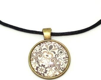 Brown and white swirls and flowers set in a bronze pendant and glass cabachon