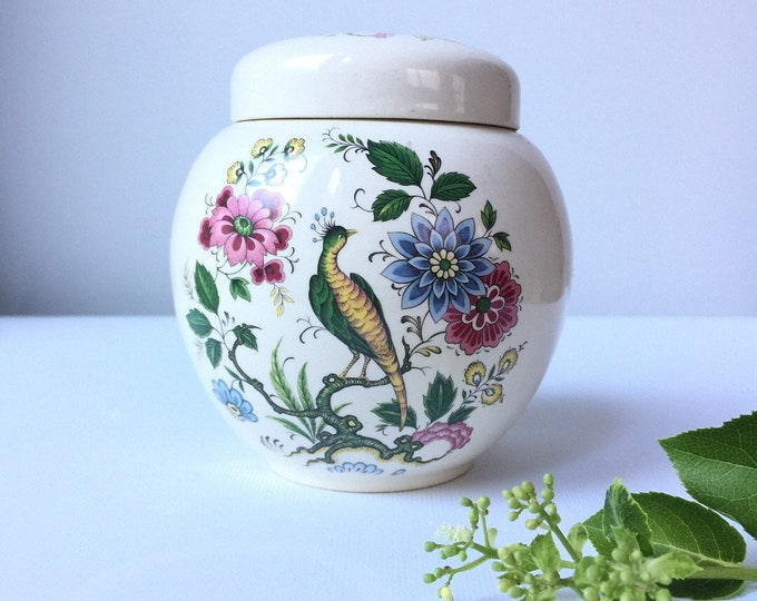 Sadler lidded ginger jar with peacock on a branch and flowers on a cream background.