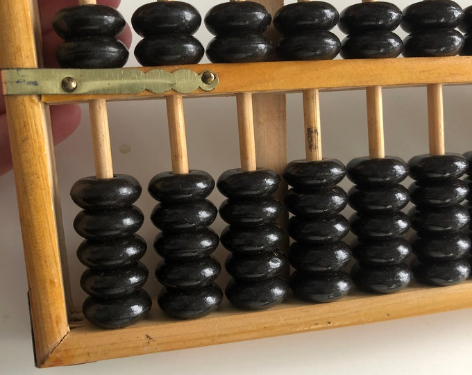 Vintage abacus with black beads. Wood with brass detail