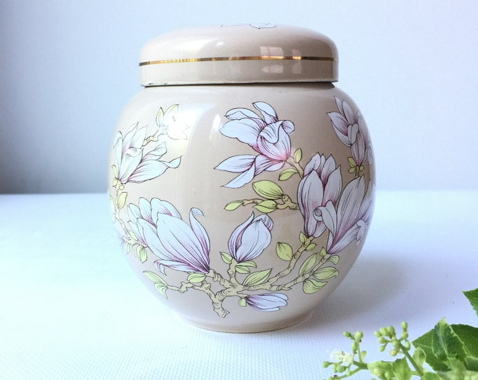 "Sadler ""Magnolia"" pattern lidded ginger jar with pale purple flowers on a beige background."