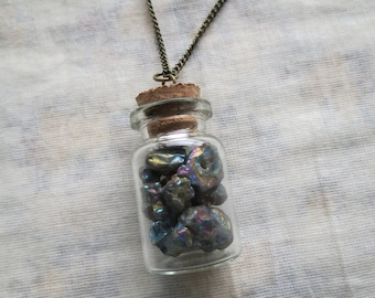 glass jar filled with rainbow titanium quartz clusters necklace