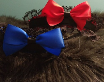 Satin ribbon, in either blue or crimson with black lace accents.