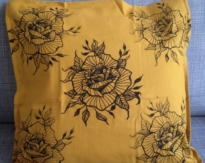 Tattoo inspired blackwork style hand screen printed rose design with repetition, mustard colour cotton cushion cover, 50cm x 50cm