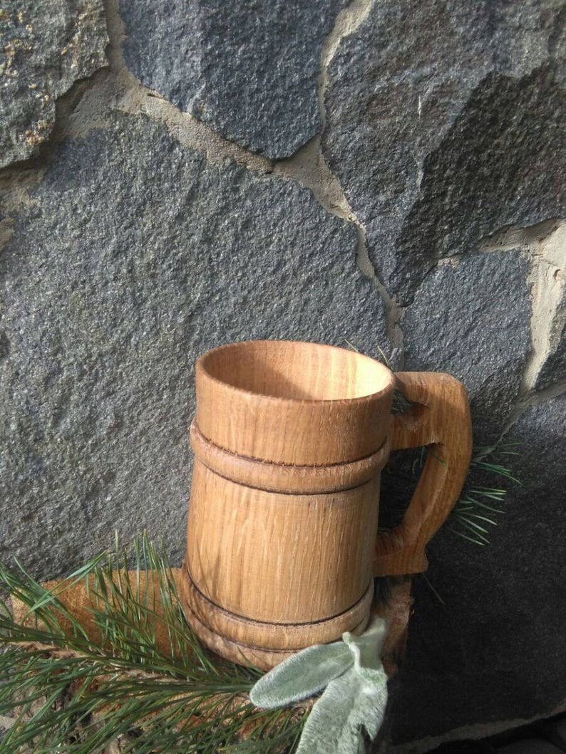 Wooden tankard in front of stone wall.