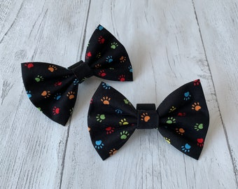 Handmade Dog Bow Ties in a gorgeous Paw Print on a black background Fabric.