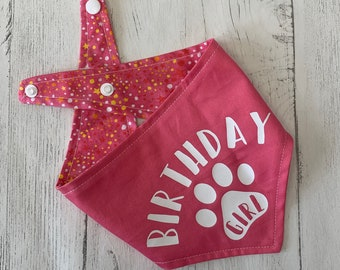 Birthday Girl Paw Print vinyl print double sided dog Bandana in bright pink with a pink, orange and white stars fabric.